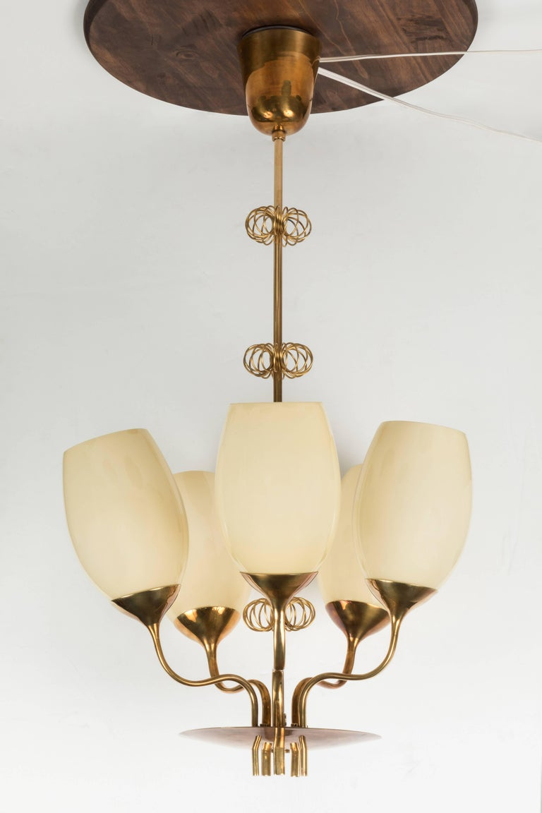 1950s Paavo Tynell five-glass chandelier for Taito Oy. A rare and unique chandelier originally owned by a doctor from the Kuopio Children's Hospital in Finland. Executed in attractively patinated brass and handblown opaline glass and whimsically