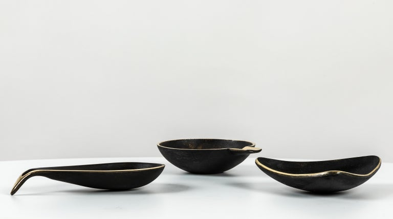 Set of three Carl Auböck brass bowls. Includes one each of Models #3904, #3844 & #4082. Designed in the 1950s, these incredibly refined and sculptural Viennese bowls are executed in polished and darkly patinated brass. Originally conceived as an