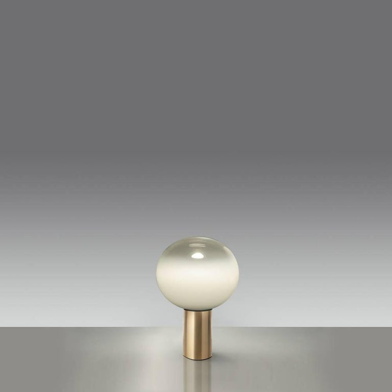Mattheo Thun 'Laguna 26' table lamp for Artemide. This lyrical design casts a warm and softly diffused light in its surrounding environment. Executed in handblown milky white glass with crystal finish at the top mounted on a gold painted aluminum