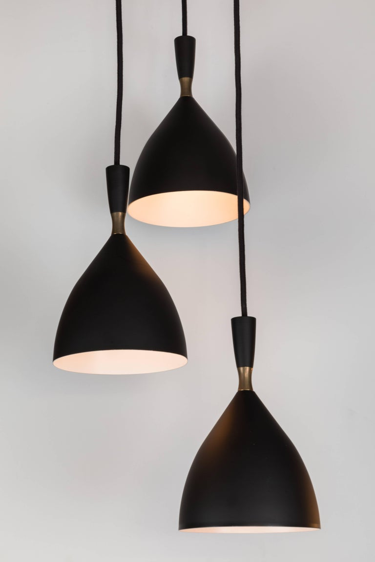 1950s Birger Dahl three-cone cascading chandelier for Sonnico, Norway. This architectural chandelier was designed in 1954 and executed in black painted metal with exquisite brass detail, custom thick black cloth cord and patinated brass ceiling