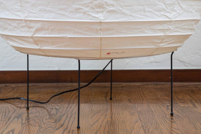 Large Isamu Noguchi Akari 23N floor lamp. Executed in handmade washi paper and bamboo ribs with Noguchi Akari manufacturer's stamp and metal legs. 