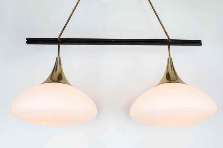 1950s Stilnovo double pendant glass and brass chandelier. A quintessentially 1950s Italian design executed in two large matte finish opaline glass pendants, painted metal and brass with original architectural ceiling canopy. A highly functional