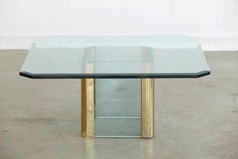 Impressive coffee table with a square base of thick glass connected to solid brass elements. The octagonal glass top is made of 3/4