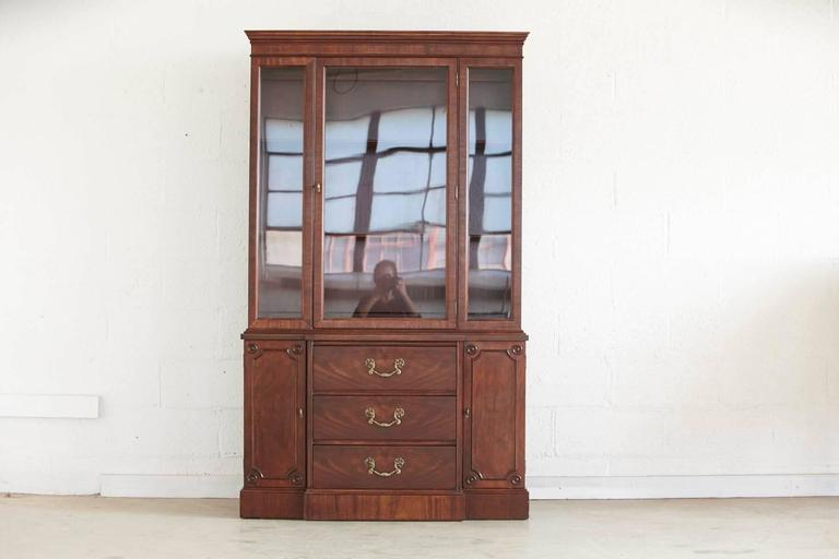 Walnut china cabinet or hutch, features a three-drawer cabinet with brass pulls and two doors and a hutch with one large glass door.