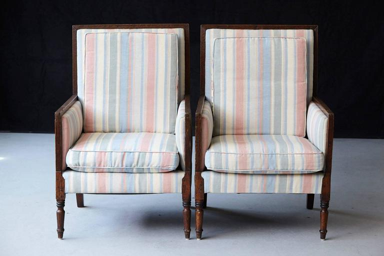 Beautiful pair of Italian neoclassical style bergères with a reeded frame raised on turned cylindrical legs. The rectangular backs and seats with loose cushions covered in pastel tone striped moiré taffeta. There are some minor, hardly visible spots