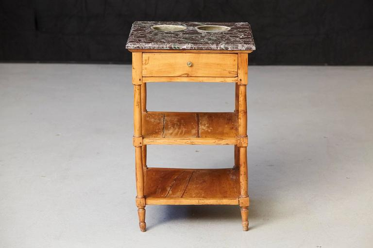 19th century French Provincial fruitwood work table having a square variegated grey and beveled marble top overhanging above a frieze with a single drawer, raised on turned columnar legs joined by two shelf stretchers. The marble top has two zinc