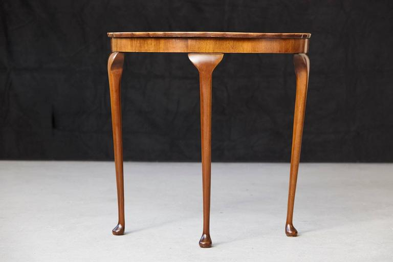 Queen Anne Revival style petite demilune walnut console table with pie crust edge. The top has one stain, please refer to the photos.