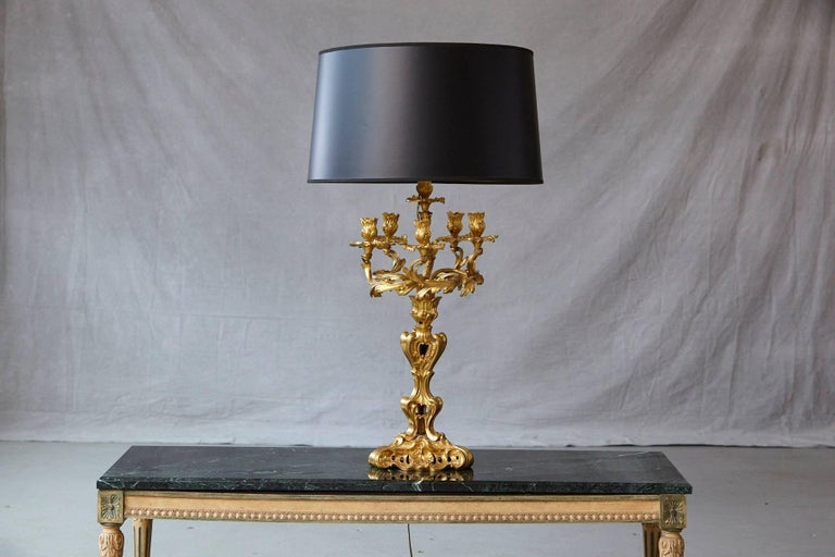 Gorgeous Louis XV style doré bronze candelabrum table lamp with six lights, the whole foliate cast, now electrified and with a new black shade with gold colored lining.