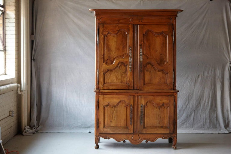 Extraordinary French 18th century Louis XV style fruitwood cabinet a deux corps. The upper section recessed and with a molded overhanging cornice above a simple paneled frieze and twin decoratively paneled cupboard doors enclosing shelving covered