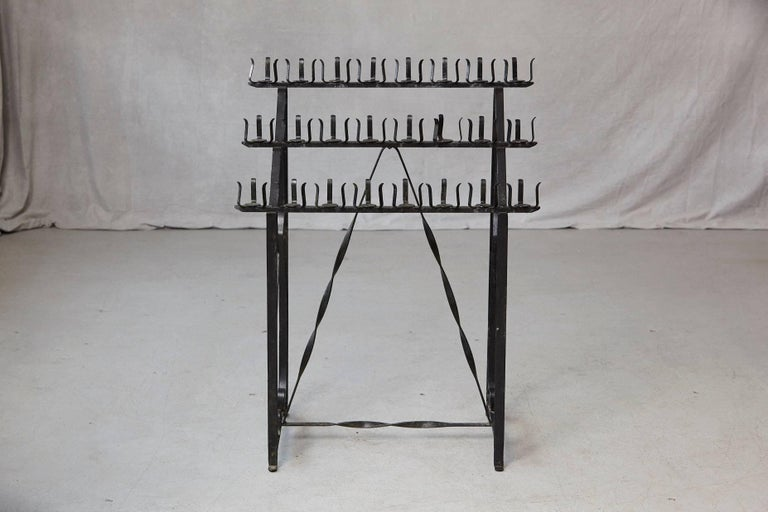 Black wrought iron votive candle stand for 24 candles. 