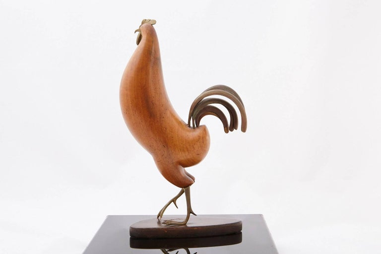 Elegant, streamlined, modernistic sculpture of a rooster by Karl Hagenauer of Vienna. The rooster's tail, feet and comb are crafted from bronze, the body hand-carved from walnut, all raised on a tinted walnut base.