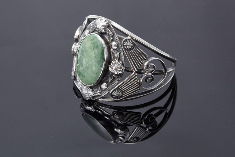 Striking sterling cuff with large centre green turquoise cabochon, surrounded by floral and dot reliefs, flanked by shooting stars and scrolled motif. Hallmarked sterling. Missing one dot around the cabochon, not really noticeable, tiny scratch to
