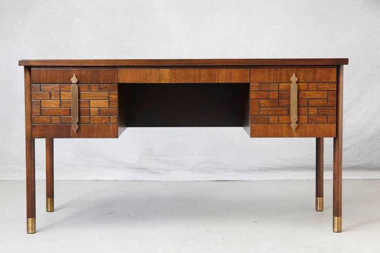 Impressive walnut desk with four drawers, graphic wood work on the drawers, wood inlays on the top and brass hardware, mounted on round legs with brass leg tips. Quality wood construction in excellent condition, circa 1970s. Height from the floor