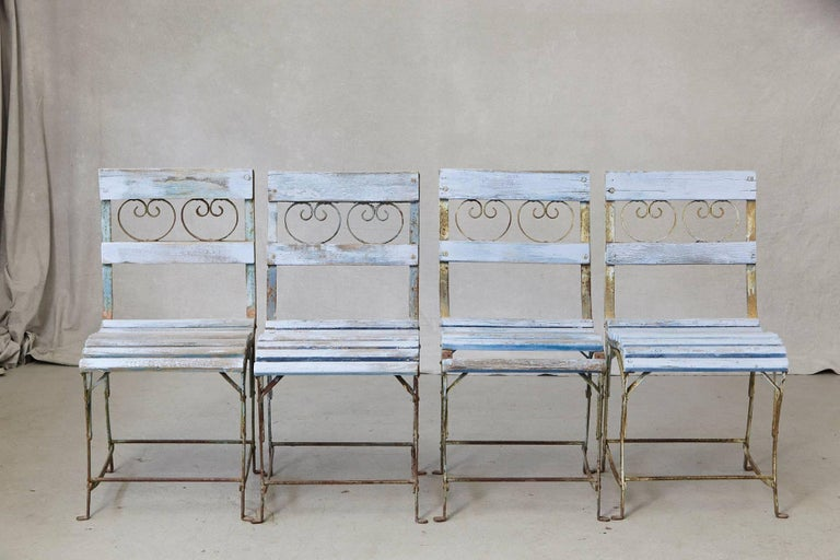 Beautiful set of four French wrought iron garden chairs with blueish wooden slats, circa 1920s. The chairs have been painted at one point in their life, the blue is faded out, there are paint chips and loss very charming look, beautifully weathered