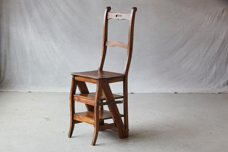 Fine example of a metamorphic fruitwood library chair which unfolds into a set of sturdy library steps, with a pierced top rail and a midrail above a solid seat and original iron brackets for stability, from France, circa 1840s. The chair is in