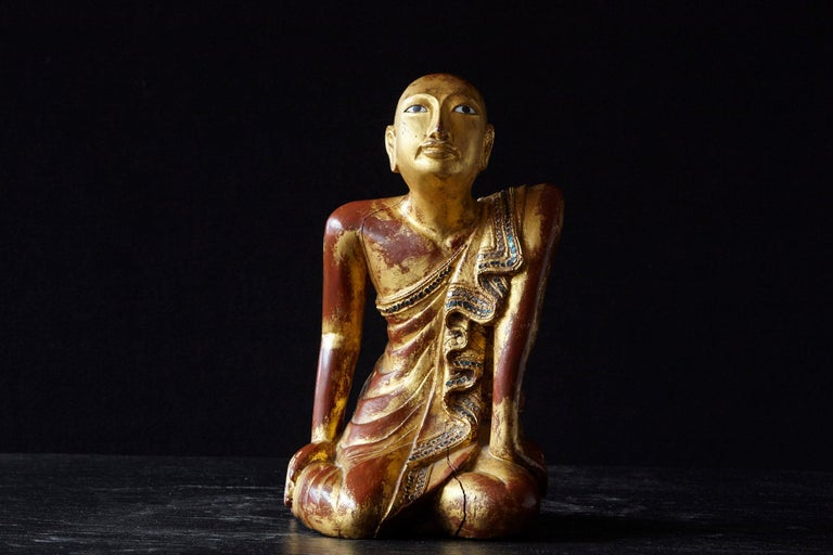 19th century gilded kneeling Burmese Buddhist monk. Carved from one single piece of teak wood, with an underlaying red paint on which the gilt lacquer was applied and with multi colored glass inlays around the edge of the cape of the monk.