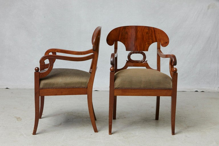 Pair of late 19th century Swedish Biedermeier or Karl Johan style birch wood armchairs with curved upper back over a wreath decor, scroll over arms and sabre legs with ball shaped finials, 