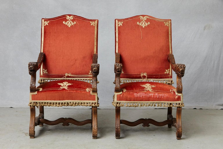Majestic pair of antique French Louis XIII, Os de Mouton, walnut throne chairs with elaborated carvings, including figural lions head arm rests, carved acanthus-leaves on scrolled arms and feet and legs joined by H-shaped stretchers. The chairs have