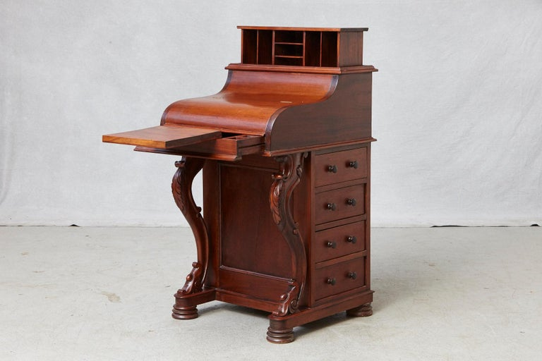 20th century walnut Davenport desk with a piano top, a flip front, a spring loaded letter compartment released with a hidden latch in a lower drawer, a plentitude of drawers, pen trays and pigeonholes for storage.  Four full width drawers on one