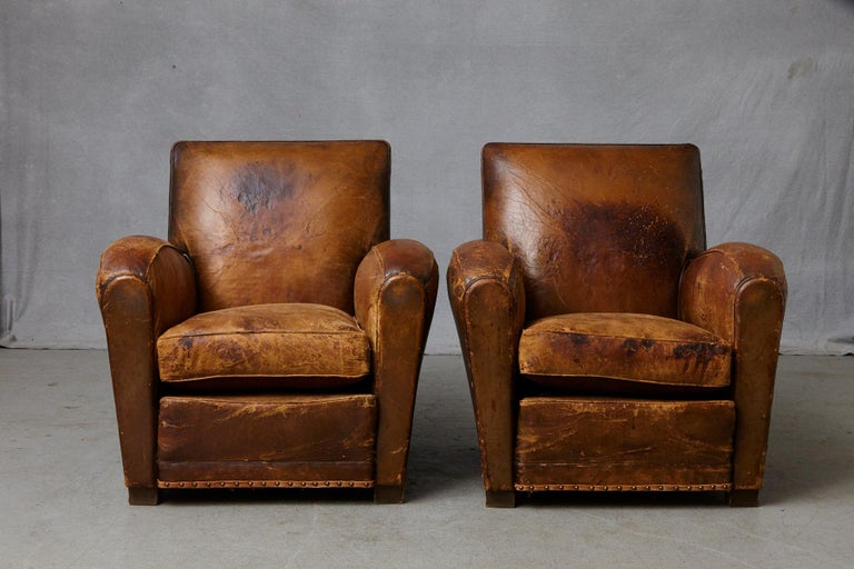 Beautifully distressed and very comfortable pair of French leather fauteuils or club chairs, circa 1930s. A few tears, repairs and rips on both chairs. Please refer to the detailed photos, as they are part of the description. Solid frame work. Very