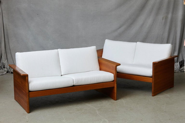 Two newly upholstered tarn stole solid teak love seats / sofas with modern Danish design details and craftsman inspired lines, circa 1970s.