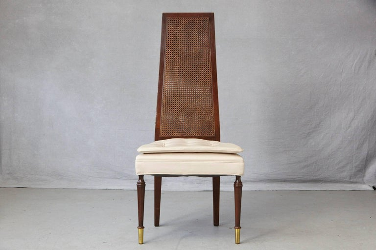 High back desk or side chair with a double-sided rattan back and a double seat cushion in beige faux leather, mounted on round legs with brass tips to the front and square legs with a slight splay in the back. The double-sided rattan back is in very