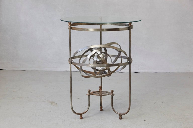Rare and exceptional kinetic side table with revolving orbital motion, England, 1930s. Steel base with a perpetual revolving orbit within the table and glass top. The inner iron ball has an engraving - Sweet Sound Steel Boom. The table has a
