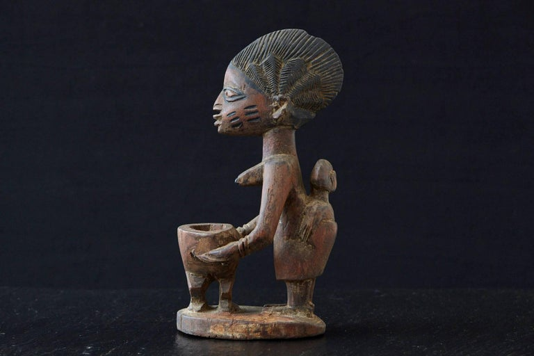 Carved wooden sculpture depicting a woman sacrificing holding an offering bowl, Yoruba People, Nigeria, 1940s  There is a small old chip on the top, please refer to the photos.   The numbers are the inventory numbers from Pennsylvania State