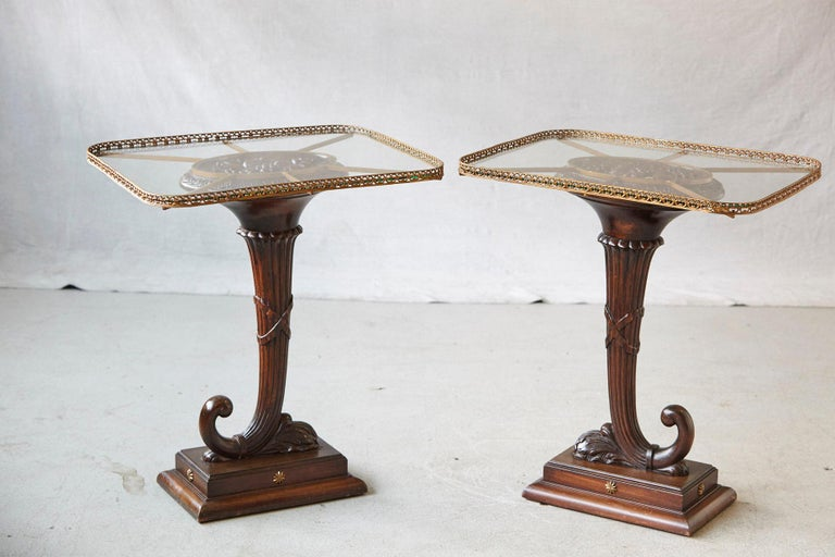 Striking pair of English early 20th century elaborately hand-carved walnut cornucopia side tables with rectangular glass tops with rounded corners based on brass supports and pierced brass galleries. Each cornucopia is mounted on a square base