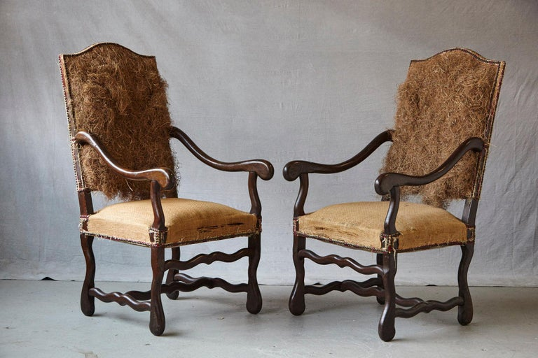 Unusual pair of Louis XIV style, Os de Mouton, walnut fauteuils restyled into this particular look by Michael Trapp, with removed upholstery, seat and rear covered in burlap, nailhead trim and exposed straw filling.