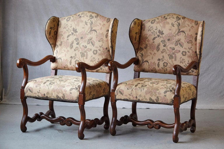Striking pair of antique French Louis XIV style, walnut wingback fauteuils with carved armrests, standing on 'os de mouton' legs joined by H-shaped stretcher base, upholstered with a tapestry like fabric with nailhead trim, nailhead trim.
