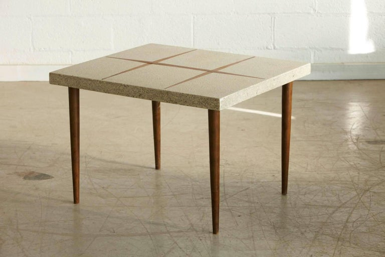Mid-Century Modern rectangular side table with cream colored terrazzo top and walnut inlays, mounted on tapered walnut legs, circa 1950s. The are a few tiny chips to the edge of the top, hardly visible because of the terrazzo pattern, please refer
