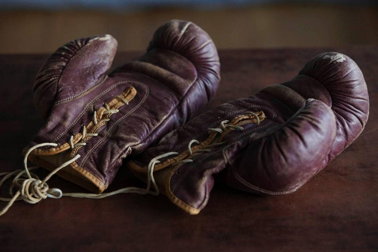 Great pair of 1930s hand stitched boxing gloves made by George A. Reach sporting goods Company. Beautiful dark maroon leather trimmed with brown edges and a nice patina.  The gloves are of highest quality for that area, the leather remains soft