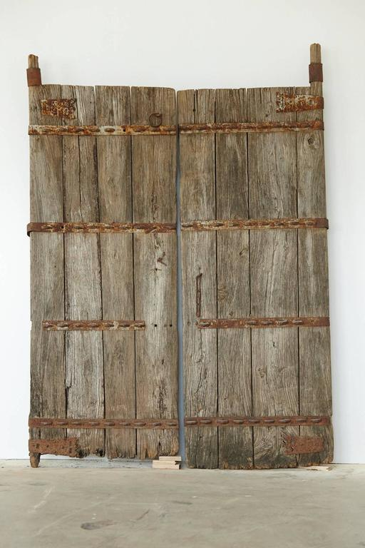 Pair of unrestored Chinese gate doors in heavy, reinforced solid oak with hand-forged metal applications. The depth of the doors is 7