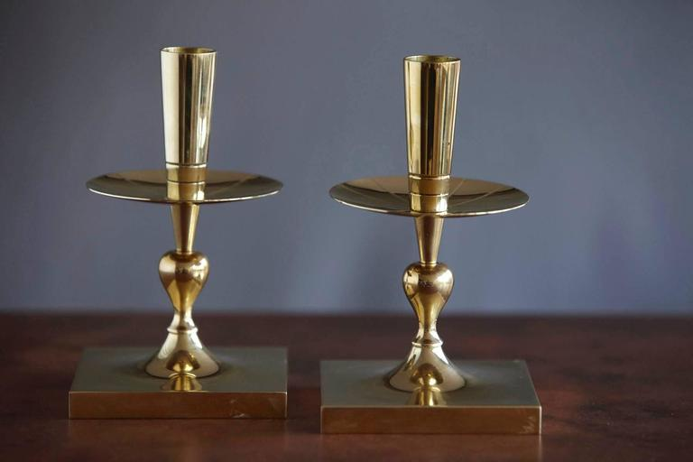 Elegant pair of Tommi Parzinger solid brass candleholders made by Dorlyn Silversmiths New York, manufacturers hallmark engraved on the bottom.