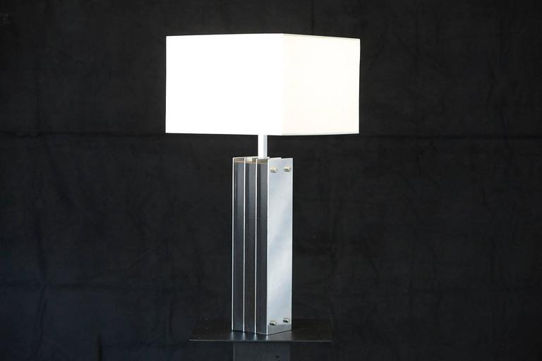 Tall table lamp with polished aluminum elements alternating with black veneered wooden elements. Good condition with a few slight scratches in the aluminum, please refer to the photos. Height to finial 33.75 in. Can be sold without shade, with a
