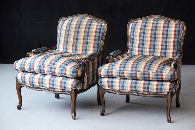 Pair of French Louis XV style bergères upholstered in a colorful madras check chintz fabric with loose down filled cushion seats.