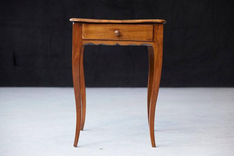 Charming late 19th century, circa 1890s, occasional table in walnut, featuring single frieze drawer, a shaped apron raised on cabriole legs.