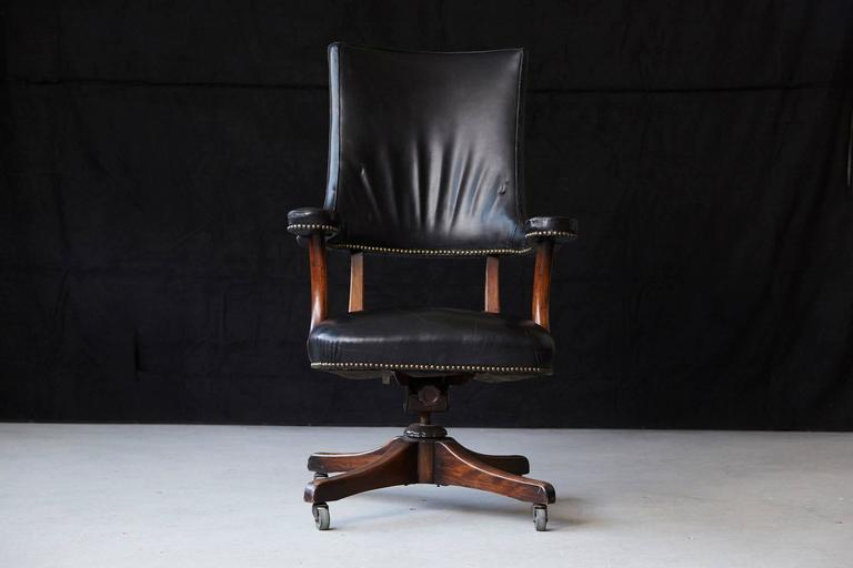 Yale Berge high quality early 1970s reproduction high back 'banker's chair on castored swivel base. Walnut frame covered in brass nail trimmed thick black leather. There is a minor, professionally exercised repair on of the armrests. Please refer to