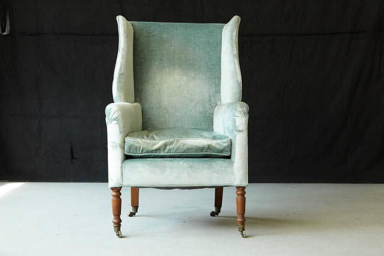 Early 19th century Hepplewhite mahogany wingback chair on brass casters,