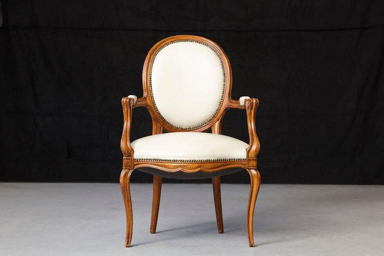 Gorgeous Louis XV style fauteuil with a molded walnut frame, having an oval back and shaped seat covered in nail trimmed creme leather and with conforming elbows rests on the shaped arms. The arms with voluted supports, shaped apron, the whole