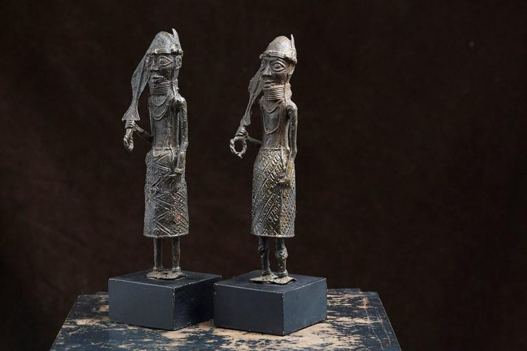 Pair of Benin iron warrior statues on black wood pedestals, dating back to the 1960s.