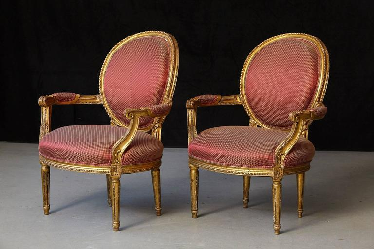 Beautiful pair of French Louis XVI style gilded fauteuils with carved relief ornaments. Some loss to the gild, please refer to the photos. Upholstery in very good condition. Very Wabi-Sabi Style.