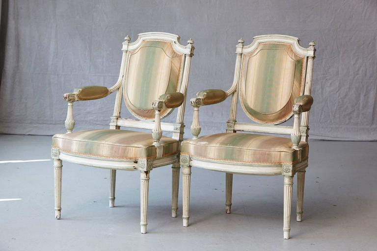 Exceptional pair of 19th century French Louis XVI style painted fauteuils. The chairs have Greek inspired geometrical fluted legs which continue in the upper back part of the frames and divert into the arms. Shield shaped seat backs. The chairs have
