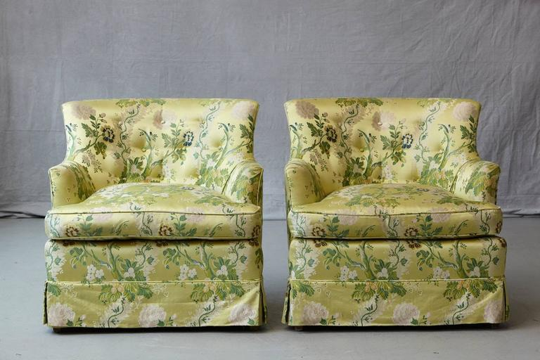 Pair of comfortable lounge chairs in summerly lime green floral chintz from ABC upholstery, with two matching pillows. One chair has a stain on the seat surface and both chairs show a little bit of wear on the corners, please refer to the detailed