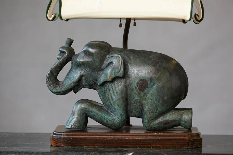 Beautiful patinated metal recumbent Indian elephant, mounted to a rosewood plinth, with a custom-made height adjustable silk shade.  The silk shade has a few tears, please refer to the photos.  Measurements shade: W 15.5 in x D 11.5 in x H 9.5