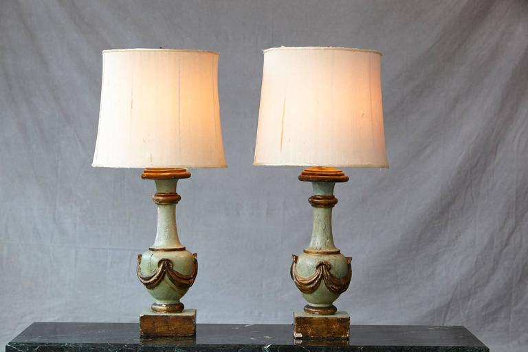 Exceptional pair of antique Italian hand-painted and hand-carved wood variform table lamps, each with an aqua and guilt finish. The draped bottle forms on squared bases. custom-made silk shades.  The lamps and shades are as is, with splits in the