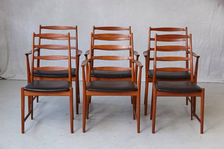 Beautiful set of six high back teak dining chairs, four armchairs, two side chairs, with original black leather seats, designed by Arne Vodder for Vamo Sønderborg, Denmark, 1960s. The fine sculpted chairs are in a very good condition, one single