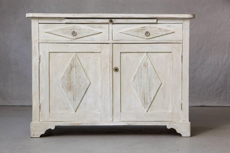 Swedish sideboard from the Gustavian period, two doors with diamond shaped and reeded carvings, which open into a single shelf. Two drawers also with diamond shaped and reeded carvings above with an additional integrated serving tray. All