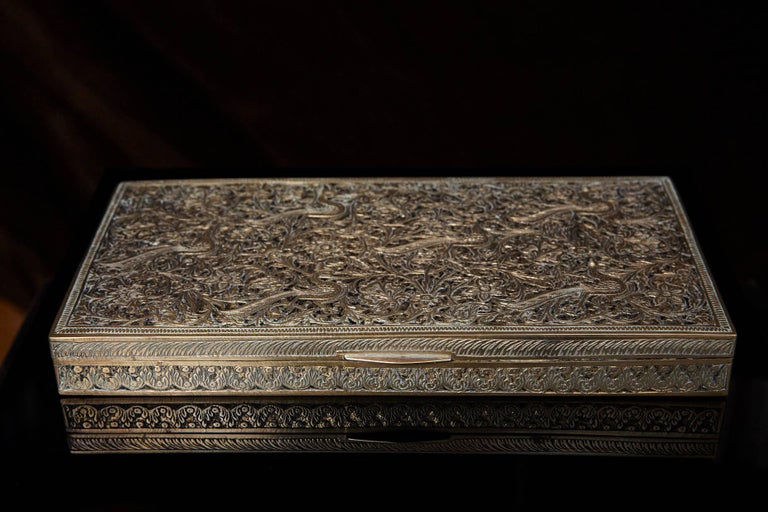 A beautiful antique Persian brass box decorated with ornate engraved designs showing a multitude of flora and fauna in elegant repeating patterns. The cedar lined box may have been designed as a tabletop cigarette box due to its wide, low design